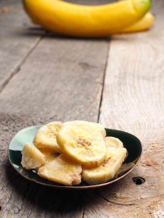 Tasty organic banana chips on a plate, healthy eating concept