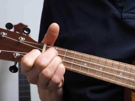 Left-handed man playing D minor reversed on a right-handed ukulele