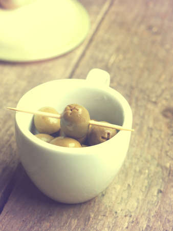 Tasty organic olives in a small white cup on a rustic wooden kitchen table, retro color stylized