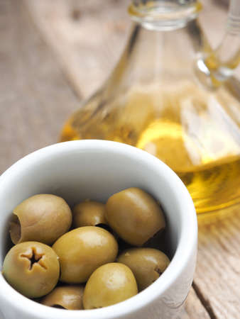 Tasty green organic olives with oil on a rustic wooden kitchen table