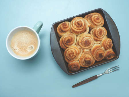 Sweet and tasty cinnamon pastry in a ceramic baking dish, view from above, modern flat tone style