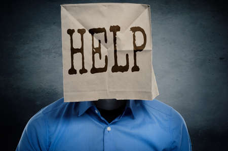 Businessman needs help, paper bag with the word help on his head, conceptual image Imagens