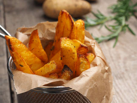Homemade fries with rosemary on a rustic wooden kitchen table Imagens