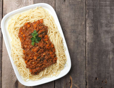 Tasty organic spaghetti with vegetarian bolognese sauce on a rustic kitchen table