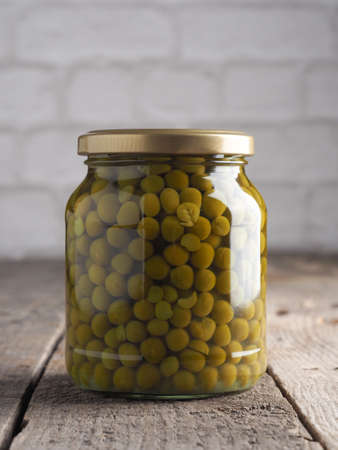 Organic peas in a mason jar on a rustic wooden kitchen table