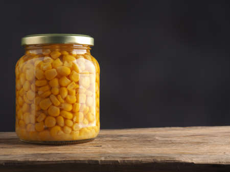 Organic corn in a mason jar on a rustic wooden table with space for text or image