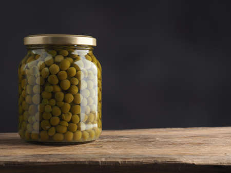 Organic peas in a jar on a rustic wooden kitchen table with space for text Imagens