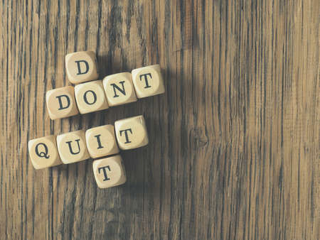 Small wooden blocks with the words Dont quit and do it, conceputal business image with space for text