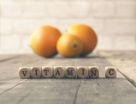The words Vitamin C on wooden blocks, orange fruits in the background, healthy eating or diet concept, flat tone stylized