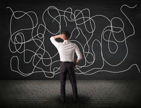 Businessman is looking at a blackboard wall , de-clutter your life concept