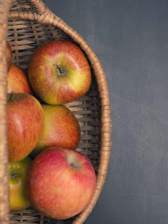 Fresh organic apples in a basket on a dark background, view from above