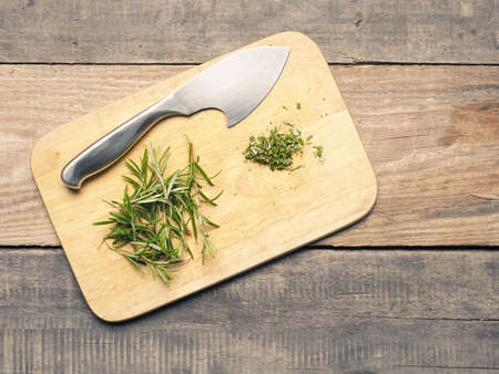 Freshly harvested and chopped rosemary on a cutting board, healthy herbs concept