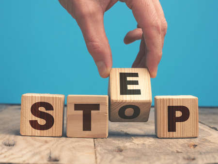 Businessman turns wooden cube with the inscription Step, Motivation or success concept, next step career concept