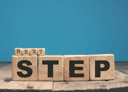 Wooden blocks with the words Next step, motivation or career concept