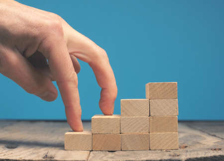 Hand of a businessman taking the next step on wooden stairs, motivation or career concept