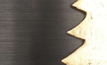Close up of a golden tree shape on a dark brushed metal background with space for text