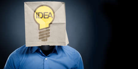 Businessman wearing a paper bag with a light bulb on it, Creativity or new ideas concept with space for text or image 版權商用圖片 - 130072749