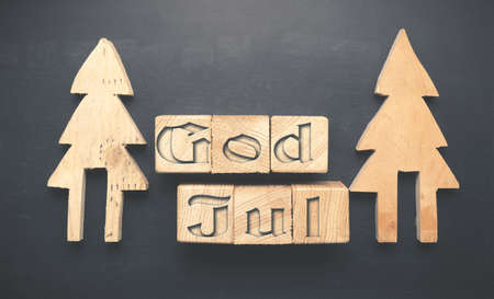 God Jul, Scandinavian Merry Christmas background with wooden tree shapes and wooden blocks on a blackboard, Christmas greetings concept Stock Photo