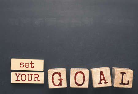 The words Set YOUR GOAL on wooden blocks on a blackboard with space for text or image