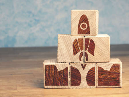 Pyramid of wooden blocks with an abstract rocket, start up concept Reklamní fotografie