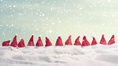 Many hats of Santa in a row with snow, Christmas background, panoramic view