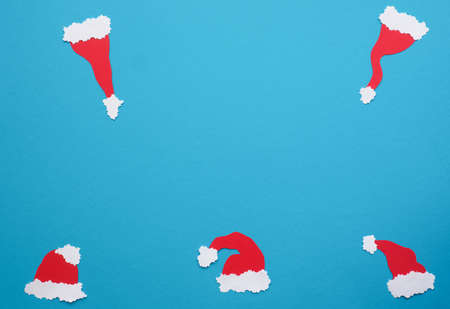 Five handmade hats of Santa on a blue paper background with space for text
