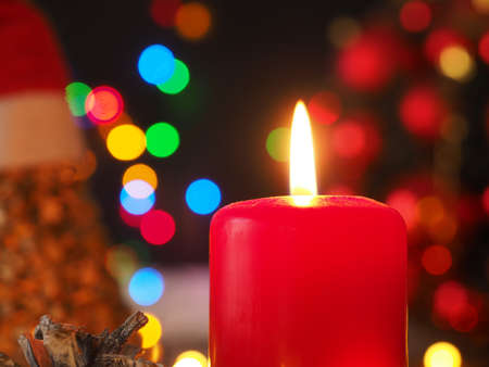 Burning Advent candle with blurred Christmas lights, beautiful romantic Christmas background