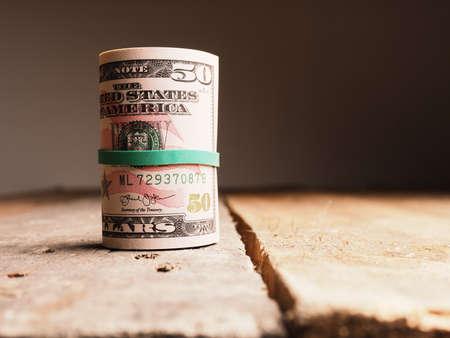 Diverse banconote in dollari su un tavolo in legno rustico, concetto di importo di reddito o risparmio