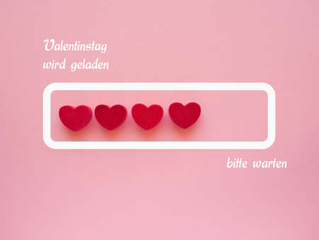 German words Valentines Day loading, please wait with red hearts on a pink paper background