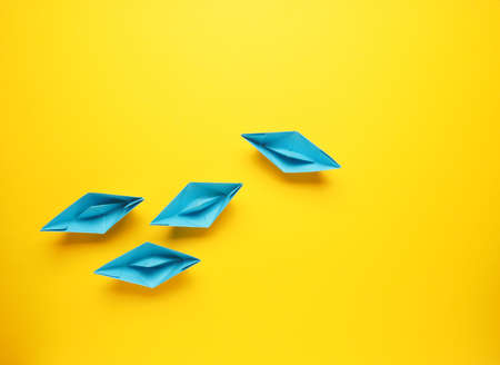 Teamwork business concept with paper boat on yellow background, view from above with space for text Stockfoto