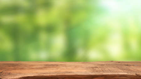 Emtpy wooden table with blurry nature background and flares, space for your text or product