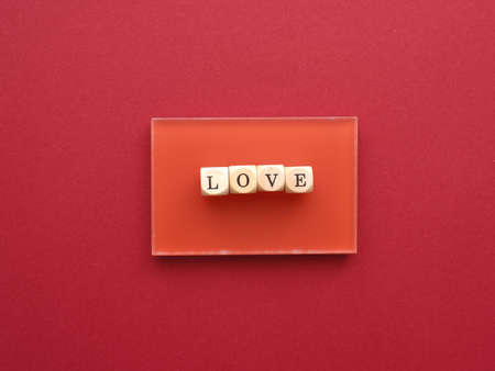 Wooden blocks with the word love on a red background, red is the color of love