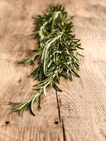 Twig of organic rosemary on a rustic wooden kitchen table, healthy food or ingredients concept