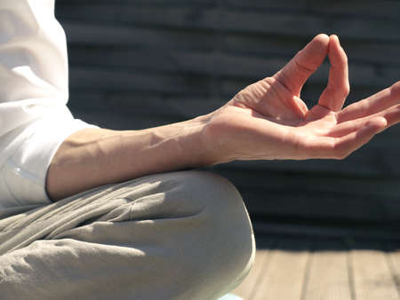 Man relaxes while meditating on a wooden terrace, close up shot with selective focus on the hand Фото со стока