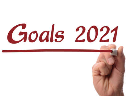 Hand writing the words Golas 2021 with a red pen on glass, business concept