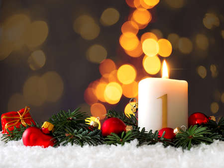 Candle of the first Advent burns, fir branches and Christmas tree balls in the snow