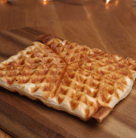 Tasty waffle from puff pastry on a wooden board, sweet food