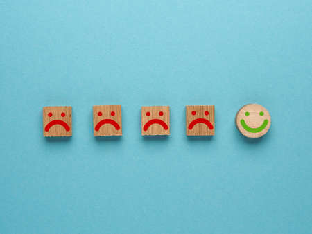 Customer service experience and satisfaction survey concept with facial expressions negative and positive on wooden cube on blue background, rating concept