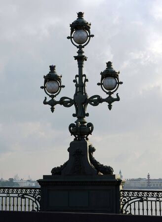 lamplight: vintage street lamp on embankment of river on sky background Stock Photo