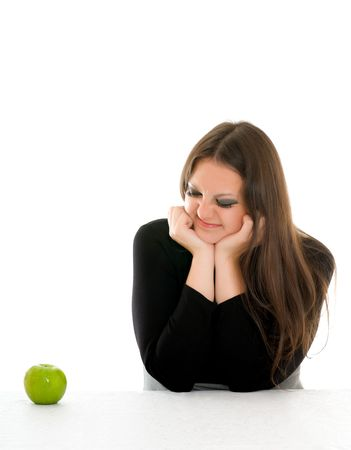 girl with grimace on her face and green apple photo