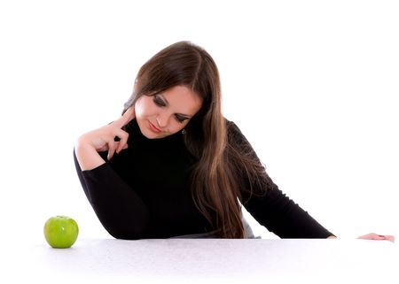 girl staring at the green apple isolated on white photo