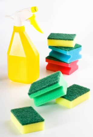 yellow spray bottle and multicolored sponges on grey background photo