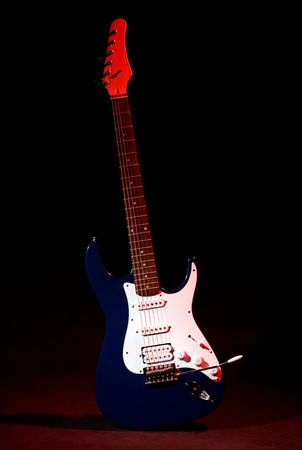 strat: electric guitar in ray of red light on black background Stock Photo