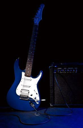 strat: electric guitar and combo amplifier in rays of blue light on black background Stock Photo