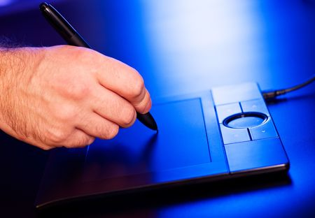 mans hand on drawing tablet in blue light Stock Photo