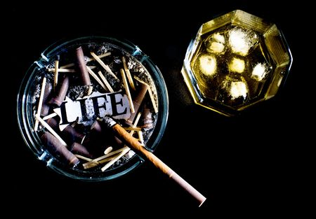 intoxicate: ashtray full of butts and glass of whiskey on black background Stock Photo