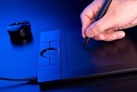 graphic tablet: mans hand draws on graphic tablet in blue light Stock Photo