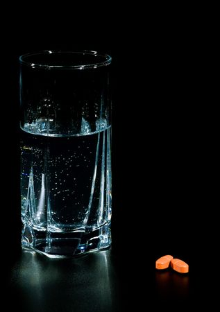 two pills and glass of water isolated on black photo