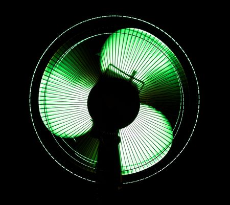airscrew: big office fan in green light isolated on black