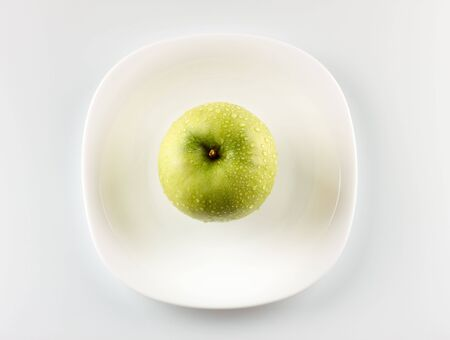 green apple on white dish grey background photo